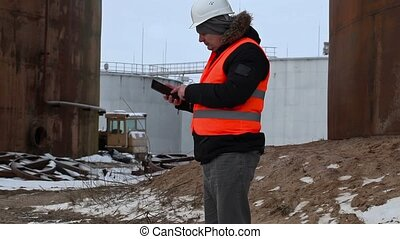 Engineer using tablet PC in the factory near to the oil...