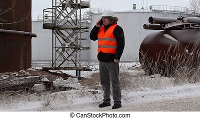 Engineer talking on the smartphone near to the oil tanks