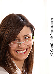 A young woman with glasses laughs