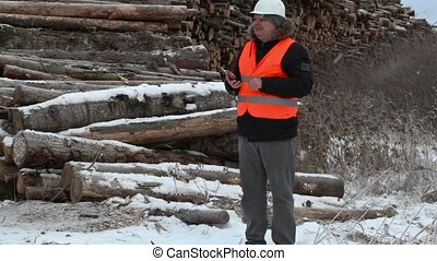 Engineer using tablet PC near to piles of logs