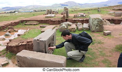 Man is looking at megalithic stone with intricate carving in...