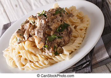 Delicious lunch: beef stroganoff with pasta close-up on a...