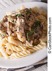 beef stroganoff with pasta fusilli closeup on a plate...