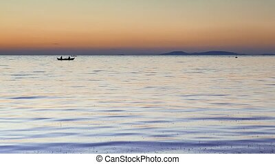 Silhouetted fisherman's boats at sunset floating calm water. 4k
