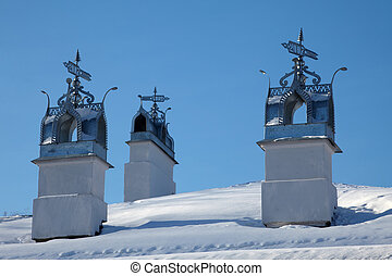 Three chimneys with elaborate latticework and weathervane -...