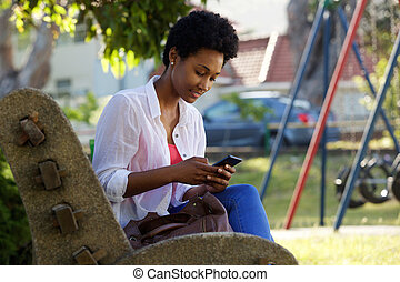 Young woman sitting on a bench sending text message -...