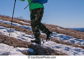 Backpacker walking on mountain peak - Low section of a male...