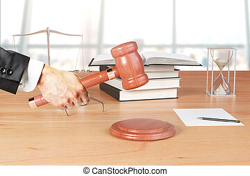 Man hand with gavel, books and hourglass on wooden table