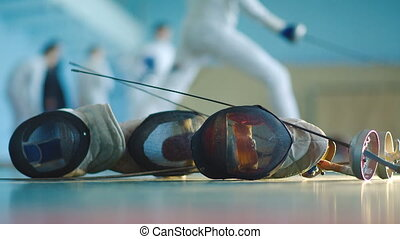 fencing mask and foil and fencers on background - equipment...
