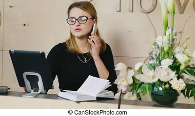 Young woman speaks on phone, taking notes on a pad