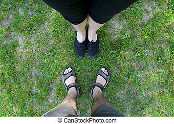 Legs on the lawn - Female and male feet on the green grass...