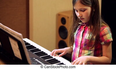 young girl playing on a synthesizer