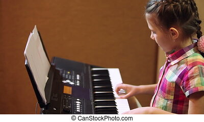 young girl playing on a synthesizer HD