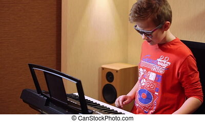 young boy playing on a synthesizer