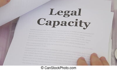 Shot of Doctor Holding Legal capacity lawsuit papers -...