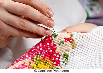Cross-stitching - Woman hands doing cross-stitch A close up...