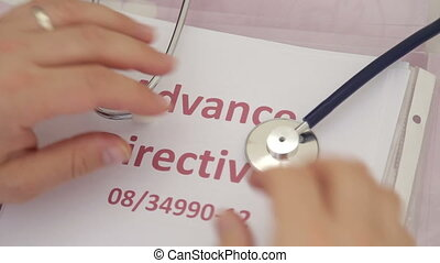Shot of Doctor holding advance directives documents -...