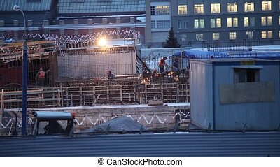 Workers at a construction site in the evening in the Russian city