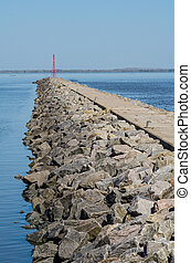 Breakwater - Large rock breakwater with a red beacon on its...
