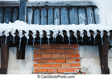 Icicles on a wooden wall - Photo of icicles hanging on old...