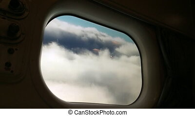 Plane window view of clouds in the sky during flight Air...