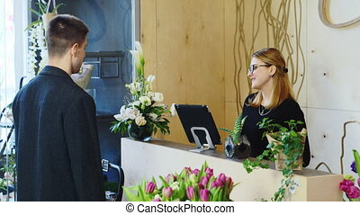 Businessman buys a bouquet at a flower shop