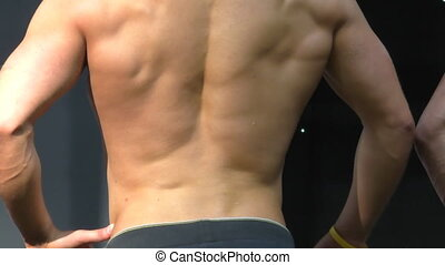 Man shows muscles at competition - Man poses showing his...