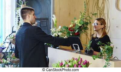 Attractive man buys a bouquet at a flower shop