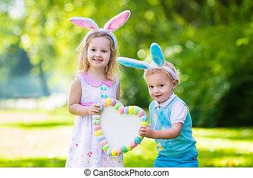 Kids having fun on Easter egg hunt - Little boy and girl...