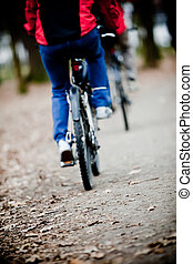 Two bicyclists going on a wood track - front focus