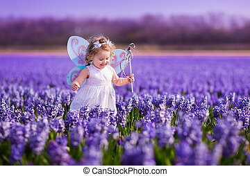 Little girl playing in hyacinth field - Cute curly little...