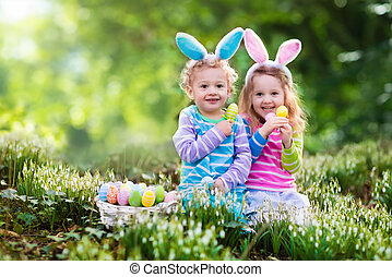 Children on Easter egg hunt - Kids on Easter egg hunt in...