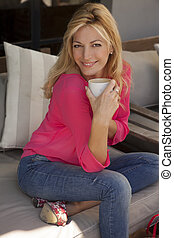 woman smiling as she holds a cup in her hands