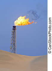 Gas Flaring In The Desert - A flare stack burning off excess...