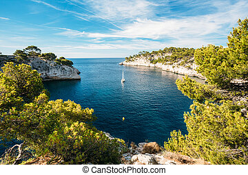 Boat leaves from bay to open sea in Calanques on the azure...
