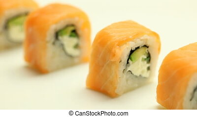 Taking sushi roll with chopsticks macro close up