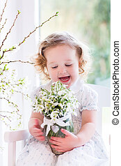 Little girl with first spring flowers at home