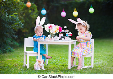 Kids playing Easter tea party with toys - Little boy and...