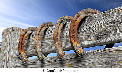 Old rusty horseshoes, set on wooden fence