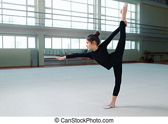 girl gymnast in a sweatsuit doing exercises the balance