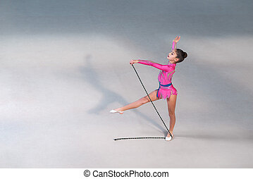 girl in dress doing exercise with gymnastic rope - Little...
