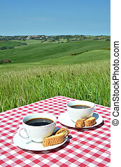 Coffee and cantuccini on the table against Tuscan landscape....