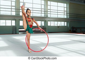 Beautiful girl gymnast performs with hoop stretch -...