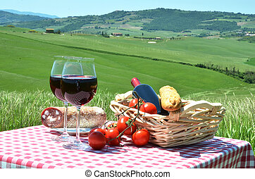 Red wine and bread on the chequered cloth against Tuscan...