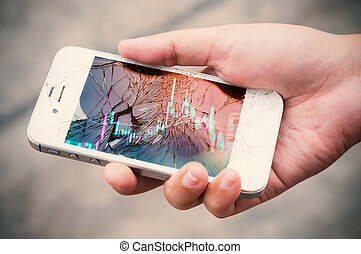 Hands holding broken mobile smartphone with stock graph...