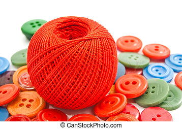 colored buttons and red ball of thread on white