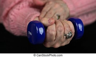 Elderly woman with dumbbell try the recovery of joints