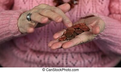 Elderly woman counting of small change coins