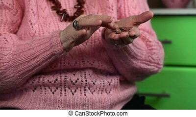 Elderly woman in pink jumper counting of small change coins