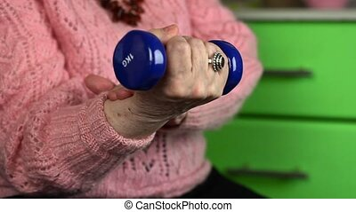 Elderly woman in pink jumper with dumbbell try the recovery...